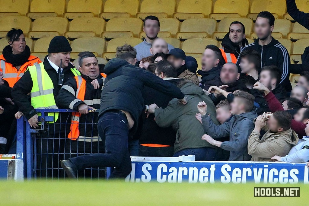A Southend United fan attacks rival Colchester United supporters during the Essex derby at Roots Hall.