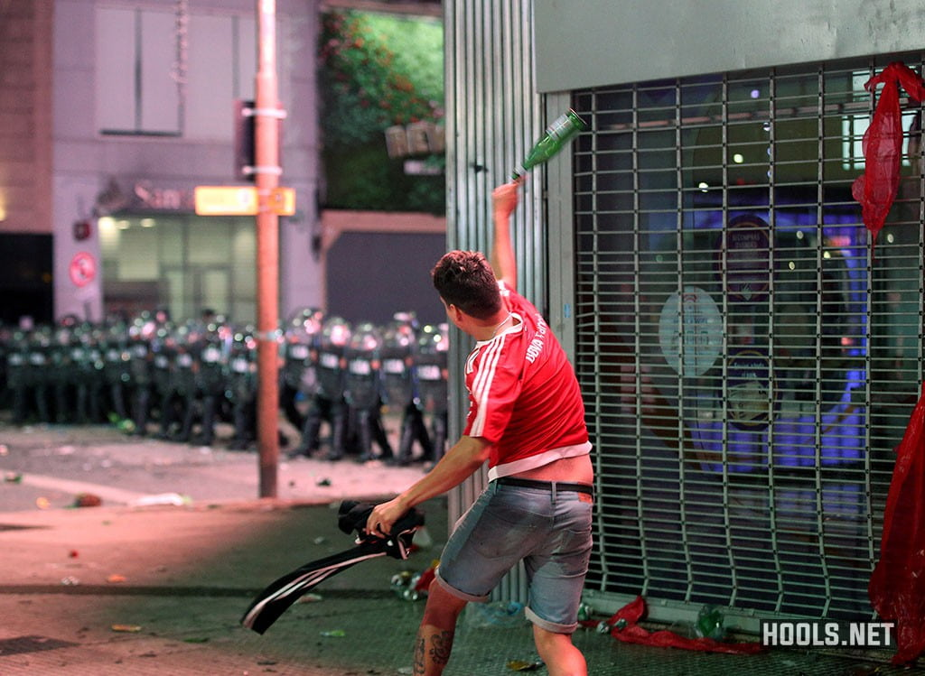 A Rive Plate fan throws a glass bottle at a line of riot cops