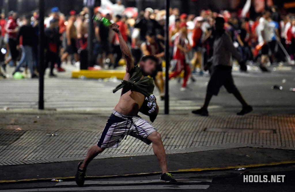 A River Plate fan throws a bottle towards riot cops