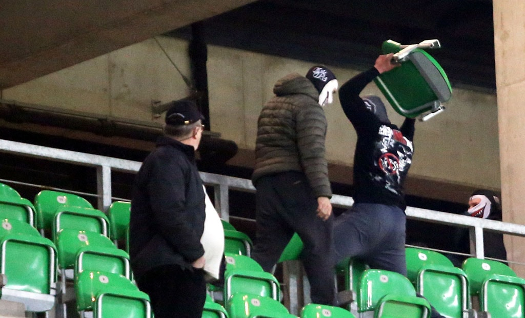 A GKS Tychy fan throws a seat towards cops